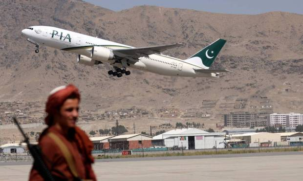 Taliban stand guard on a Pakistan International Airlines plane, the first international commercial flight to land since the Taliban regained power last month, with passengers on board at Kabul airport.  Photo: Karim Sahib/AFP