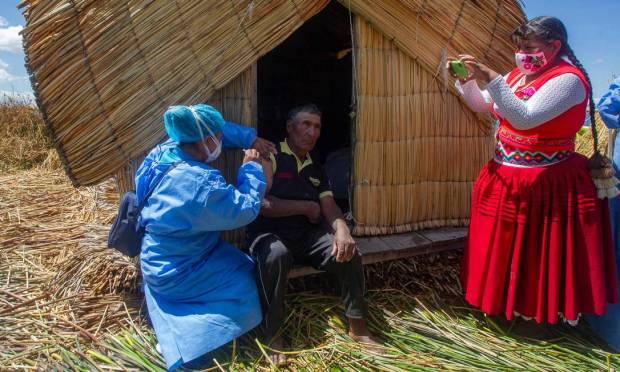 A Peruvian Ministry of Health worker vaccinated a local resident against Covid-19 alongside former Uros mayor, Rita Subana, during a program to vaccinate at-risk residents on the floating island of Uros in Lake Titicaca, Peru. Photo: CARLOS MAMANI / AFP