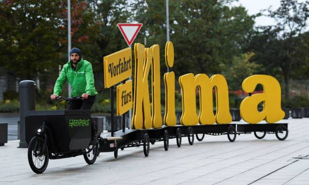 A Greenpeace protester rides a bicycle with a message on it