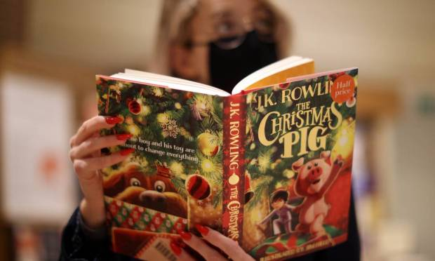 A saleswoman in a London bookstore with a copy of & # 034;  The Christmas Pig & # 034;  (' Jack eo Porquinho de Natal', in Brazil), a new children's book written by JK Rowling, author of Harry Potter Photo: HANNAH MCKAY / REUTERS
